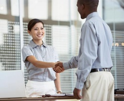 Picture of a woman colleague and male colleague shaking hands in an office